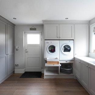 Bild på ett stort vintage grå grått kök, med skåp i shakerstil, vita skåp, marmorbänkskiva, grått stänkskydd, stänkskydd i marmor, vita vitvaror, mellanmörkt trägolv, en köksö och brunt golv