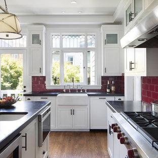 サンフランシスコの大きいヴィクトリアン調のおしゃれなキッチン (エプロンフロントシンク、シェーカースタイル扉のキャビネット、白いキャビネット、赤いキッチンパネル、サブウェイタイルのキッチンパネル、シルバーの調理設備の、濃色無垢フローリング、茶色い床、クオーツストーンカウンター) の写真