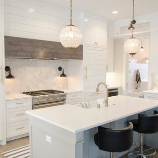 This is an example of a medium sized classic l-shaped kitchen in Devon with white cabinets, an island, a belfast sink, beaded cabinets, grey splashback, marble splashback, stainless steel appliances, light hardwood flooring, brown floors and white worktops.