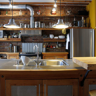 Kitchen - industrial galley kitchen idea in Montreal with a drop-in sink, recessed-panel cabinets, medium tone wood cabinets, wood countertops and stainless steel appliances