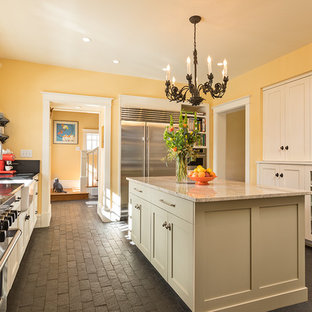 Photo of a large traditional galley enclosed kitchen in Albuquerque with a belfast sink, shaker cabinets, beige cabinets, stainless steel appliances, brick flooring, an island, black floors and soapstone worktops.