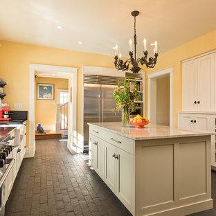 Klassisk inredning av ett avskilt, stort parallellkök, med en rustik diskho, skåp i shakerstil, beige skåp, rostfria vitvaror, tegelgolv, en köksö, svart golv och bänkskiva i täljsten