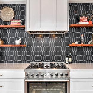 Foto di una cucina tradizionale con ante in stile shaker, ante bianche, paraspruzzi nero, elettrodomestici in acciaio inossidabile e top grigio