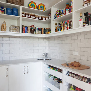 Design ideas for a large country l-shaped kitchen pantry in Melbourne with white cabinets, white splashback, subway tile splashback, light hardwood floors, a drop-in sink, beaded inset cabinets, solid surface benchtops, stainless steel appliances and with island.