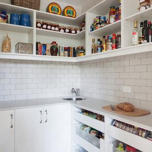 Große Landhausstil Küche in L-Form mit Vorratsschrank, weißen Schränken, Küchenrückwand in Weiß, Rückwand aus Metrofliesen, hellem Holzboden, Einbauwaschbecken, Kassettenfronten, Mineralwerkstoff-Arbeitsplatte, Küchengeräten aus Edelstahl und Kücheninsel in Melbourne