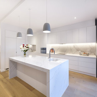 Large contemporary l-shaped kitchen in Melbourne with an undermount sink, flat-panel cabinets, white cabinets, grey splashback, panelled appliances, with island, beige floor and white benchtop.