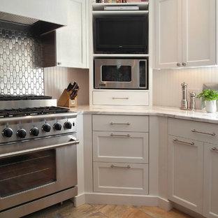 Inredning av ett klassiskt kök, med luckor med infälld panel, vita skåp, stänkskydd med metallisk yta, stänkskydd i metallkakel och rostfria vitvaror