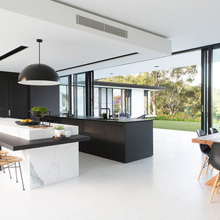 Inspiration för ett funkis svart svart kök, med en undermonterad diskho, släta luckor, svarta skåp, integrerade vitvaror, flera köksöar och vitt golv