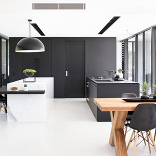 Design ideas for a contemporary galley eat-in kitchen in Sunshine Coast with an undermount sink, flat-panel cabinets, black cabinets, black splashback, multiple islands, white floor and white benchtop.