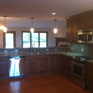 Eat-in kitchen - traditional eat-in kitchen idea in Other with raised-panel cabinets and a peninsula