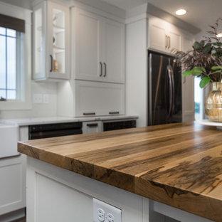 他の地域のカントリー風おしゃれなキッチン (エプロンフロントシンク、フラットパネル扉のキャビネット、ターコイズのキャビネット、木材カウンター、白いキッチンパネル、磁器タイルのキッチンパネル、シルバーの調理設備の、茶色いキッチンカウンター) の写真