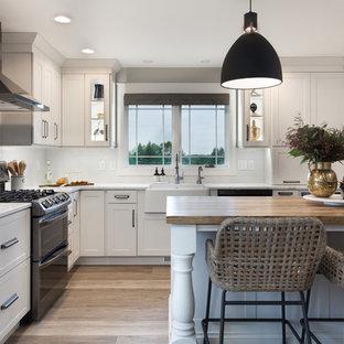 他の地域のカントリー風おしゃれなキッチン (エプロンフロントシンク、フラットパネル扉のキャビネット、木材カウンター、白いキッチンパネル、磁器タイルのキッチンパネル、シルバーの調理設備の、茶色いキッチンカウンター、ターコイズのキャビネット) の写真