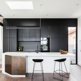 This is an example of a contemporary l-shaped kitchen in Sydney with medium hardwood floors, brown floor, an integrated sink, flat-panel cabinets, black cabinets, black splashback, panelled appliances, with island and white benchtop.