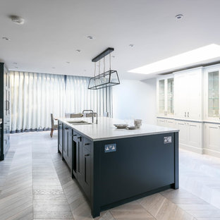 Huge transitional open concept kitchen ideas - Example of a huge transitional single-wall light wood floor open concept kitchen design in London with a double-bowl sink, beaded inset cabinets, blue cabinets, marble countertops, paneled appliances and an island