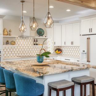 This is an example of a mid-sized transitional l-shaped open plan kitchen in Seattle with an undermount sink, shaker cabinets, white cabinets, granite benchtops, multi-coloured splashback, porcelain splashback, white appliances, vinyl floors, with island, brown floor and beige benchtop.