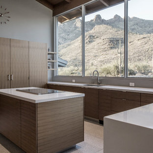 Design ideas for a large modern u-shaped kitchen/diner in Phoenix with flat-panel cabinets, brown cabinets, engineered stone countertops, integrated appliances, terrazzo flooring, white floors, a submerged sink and an island.