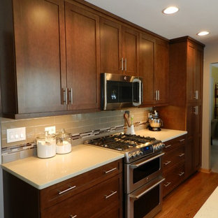 Photo of a medium sized classic l-shaped kitchen pantry in Chicago with a submerged sink, shaker cabinets, brown cabinets, engineered stone countertops, beige splashback, porcelain splashback, stainless steel appliances, dark hardwood flooring and a breakfast bar.