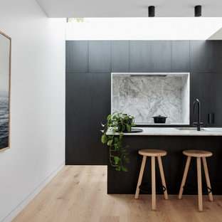 Mid-sized contemporary galley kitchen in Sydney with an integrated sink, flat-panel cabinets, black cabinets, grey splashback, panelled appliances, light hardwood floors, a peninsula, beige floor and grey benchtop.