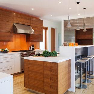 サンフランシスコのコンテンポラリースタイルのおしゃれなキッチン (フラットパネル扉のキャビネット、中間色木目調キャビネット、オレンジのキッチンパネル、ガラス板のキッチンパネル、シルバーの調理設備、淡色無垢フローリング) の写真