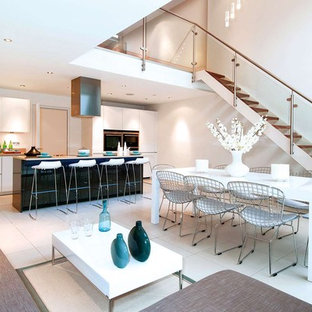 Photo of an expansive modern open plan kitchen in London with flat-panel cabinets, white cabinets, granite worktops, stainless steel appliances, porcelain flooring and an island.