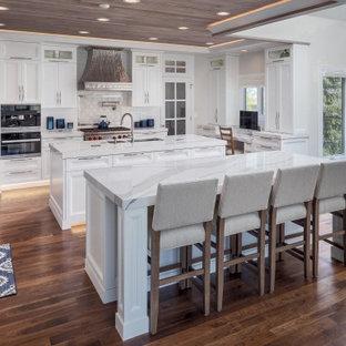 デンバーの広いトランジショナルスタイルのおしゃれなキッチン (アンダーカウンターシンク、シェーカースタイル扉のキャビネット、白いキャビネット、クオーツストーンカウンター、白いキッチンパネル、シルバーの調理設備、無垢フローリング、茶色い床、白いキッチンカウンター) の写真