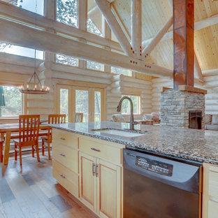 Inspiration för mycket stora rustika flerfärgat kök, med brunt golv, laminatgolv, en trippel diskho, släta luckor, skåp i ljust trä, granitbänkskiva, svarta vitvaror och en halv köksö