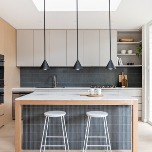 Contemporary u-shaped kitchen in Sydney with a drop-in sink, flat-panel cabinets, white cabinets, grey splashback, panelled appliances, light hardwood floors, beige floor and white benchtop.