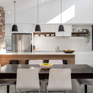 Design ideas for a mid-sized industrial galley open plan kitchen in Perth with concrete floors, flat-panel cabinets, white cabinets, white splashback, subway tile splashback, a peninsula, grey floor and white benchtop.
