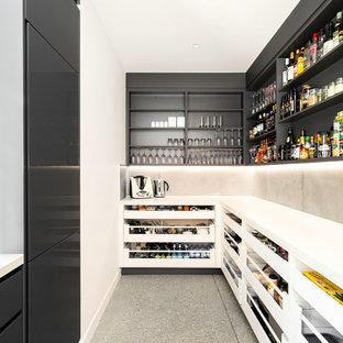 Diseño de cocina en L, contemporánea, sin isla, con despensa, armarios abiertos, puertas de armario negras, salpicadero de azulejos de cemento, suelo gris y encimeras blancas