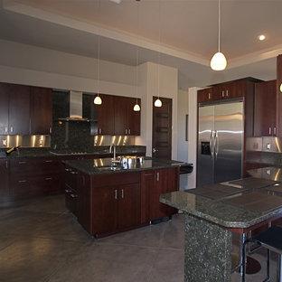 Esempio di una grande cucina design con lavello sottopiano, ante lisce, ante in legno scuro, top in granito, paraspruzzi verde, paraspruzzi con piastrelle di metallo, elettrodomestici in acciaio inossidabile, pavimento in cemento e 2 o più isole