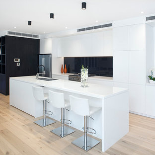 This is an example of a mid-sized contemporary l-shaped eat-in kitchen in Sydney with flat-panel cabinets, white cabinets, solid surface benchtops, black splashback, stainless steel appliances, medium hardwood floors and an island.