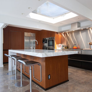 Large contemporary kitchen appliance - Kitchen - large contemporary l-shaped concrete floor and brown floor kitchen idea in Orange County with flat-panel cabinets, medium tone wood cabinets, metallic backsplash, an undermount sink, marble countertops, stainless steel appliances and an island