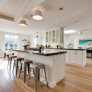 Mid-sized traditional open concept kitchen designs - Open concept kitchen - mid-sized traditional single-wall light wood floor and brown floor open concept kitchen idea in Orange County with glass-front cabinets, white cabinets, an island and stainless steel appliances