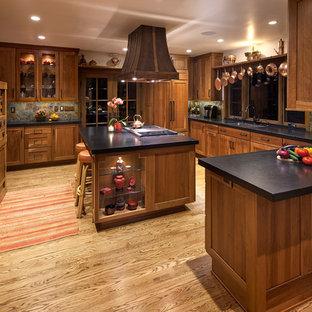 サンタバーバラの中くらいのアジアンスタイルのおしゃれなキッチン (アンダーカウンターシンク、シェーカースタイル扉のキャビネット、中間色木目調キャビネット、御影石カウンター、マルチカラーのキッチンパネル、石タイルのキッチンパネル、パネルと同色の調理設備、無垢フローリング) の写真