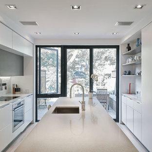 トロントの中くらいのコンテンポラリースタイルのおしゃれなキッチン (アンダーカウンターシンク、フラットパネル扉のキャビネット、白いキャビネット、銅製カウンター、白いキッチンパネル、レンガのキッチンパネル、パネルと同色の調理設備、淡色無垢フローリング) の写真