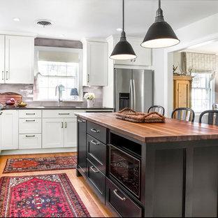 リッチモンドの中くらいのエクレクティックスタイルのおしゃれなキッチン (アンダーカウンターシンク、シェーカースタイル扉のキャビネット、白いキャビネット、木材カウンター、グレーのキッチンパネル、セラミックタイルのキッチンパネル、シルバーの調理設備、無垢フローリング、茶色い床) の写真
