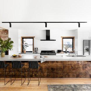 Diseño de cocina de galera, industrial, de tamaño medio, abierta, con fregadero encastrado, electrodomésticos de acero inoxidable, suelo de madera clara, una isla, armarios con paneles lisos, puertas de armario blancas, encimera de cemento, salpicadero blanco y suelo beige