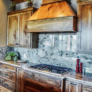ダラスの広いサンタフェスタイルのおしゃれなキッチン (アンダーカウンターシンク、シェーカースタイル扉のキャビネット、中間色木目調キャビネット、御影石カウンター、石スラブのキッチンパネル、シルバーの調理設備、濃色無垢フローリング、茶色い床) の写真