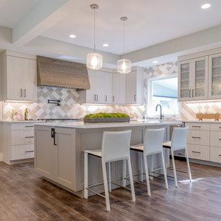 Offene, Große Moderne Küche in L-Form mit Landhausspüle, flächenbündigen Schrankfronten, grauen Schränken, Quarzwerkstein-Arbeitsplatte, Küchenrückwand in Grau, Rückwand aus Porzellanfliesen, Küchengeräten aus Edelstahl, Laminat, grauem Boden, weißer Arbeitsplatte und Kücheninsel in Denver
