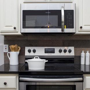 Foto på ett mellanstort lantligt svart kök, med en undermonterad diskho, luckor med upphöjd panel, vita skåp, granitbänkskiva, brunt stänkskydd, stänkskydd i trä, rostfria vitvaror, heltäckningsmatta, en köksö och beiget golv
