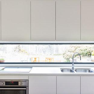 На фото: маленькая параллельная кухня-гостиная в стиле модернизм с двойной раковиной, плоскими фасадами, белыми фасадами, столешницей из кварцевого агломерата, фартуком с окном, техникой из нержавеющей стали, полом из бамбука, островом и коричневым полом
