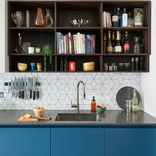 Moderne Küche mit Unterbauwaschbecken, flächenbündigen Schrankfronten, blauen Schränken, Küchenrückwand in Weiß und grauer Arbeitsplatte in London