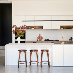 Photo of a large contemporary l-shaped kitchen in Geelong with an undermount sink, flat-panel cabinets, white cabinets, black appliances, with island, grey floor, white benchtop, white splashback and concrete floors.