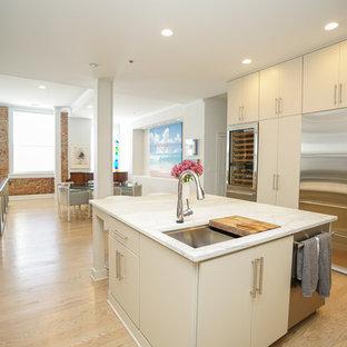 Offene Klassische Küche in U-Form mit Unterbauwaschbecken, flächenbündigen Schrankfronten, beigen Schränken, Marmor-Arbeitsplatte, Küchenrückwand in Grau, Rückwand aus Holz, Küchengeräten aus Edelstahl, hellem Holzboden, Kücheninsel und gelbem Boden in Sonstige