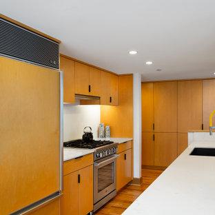 シアトルのモダンスタイルのおしゃれなキッチン (エプロンフロントシンク、フラットパネル扉のキャビネット、中間色木目調キャビネット、大理石カウンター、白いキッチンパネル、大理石のキッチンパネル、シルバーの調理設備、無垢フローリング、茶色い床、白いキッチンカウンター) の写真