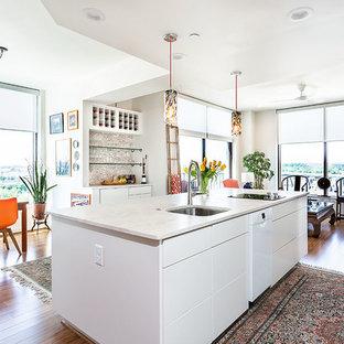 Стильный дизайн: маленькая параллельная кухня-гостиная в стиле современная классика с одинарной раковиной, плоскими фасадами, белыми фасадами, столешницей из кварцита, бежевым фартуком, фартуком из каменной плитки, белой техникой, полом из бамбука, островом, коричневым полом и бежевой столешницей - последний тренд