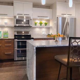 ミネアポリスの小さいコンテンポラリースタイルのおしゃれなキッチン (アンダーカウンターシンク、フラットパネル扉のキャビネット、中間色木目調キャビネット、クオーツストーンカウンター、グレーのキッチンパネル、セラミックタイルのキッチンパネル、シルバーの調理設備、クッションフロア) の写真