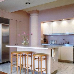 ニューヨークの広いモダンスタイルのおしゃれなキッチン (ドロップインシンク、フラットパネル扉のキャビネット、白いキャビネット、ピンクのキッチンパネル、シルバーの調理設備、セラミックタイルの床、タイルカウンター、ガラスタイルのキッチンパネル、白い床) の写真