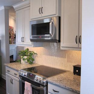他の地域の小さいエクレクティックスタイルのおしゃれなキッチン (エプロンフロントシンク、フラットパネル扉のキャビネット、グレーのキャビネット、御影石カウンター、ベージュキッチンパネル、ボーダータイルのキッチンパネル、シルバーの調理設備の、濃色無垢フローリング) の写真