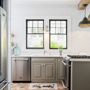 Идея дизайна: угловая кухня среднего размера в стиле кантри с фасадами с выступающей филенкой, серыми фасадами, белым фартуком, фартуком из плитки кабанчик, обеденным столом, столешницей из кварцита, техникой из нержавеющей стали, полуостровом, одинарной раковиной и кирпичным полом